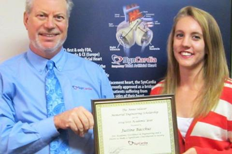 A man in a blue shirt hands a framed certificate to a woman wearing a red-and-white striped shirt.