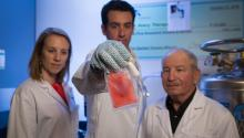 Three doctors posing with a sample of tissue