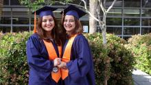 Two women in matching graduation caps and gowns hold hands in a courtyard.