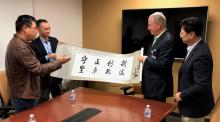 Professors from Beijing Normal University present a banner to the University of Arizona interim dean of the College of Medicine and the UA librarian