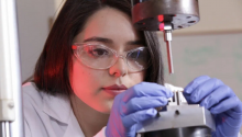 A woman wearing a lab coat and goggles focuses her attention on a small metal object.