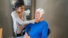 A woman straps a white cap onto an older man's head.