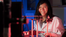 Judith Su wearing a lab coat and smiling. There is a sensor setup made of metal rods on the table in front of her.