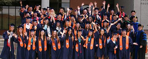 BME Class of 2016 standing on the steps of the Center for Creative Photography in caps and gowns