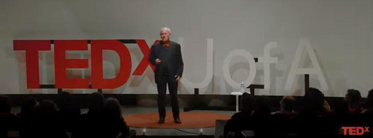 Screen capture of video of David Galbraith on stage at TEDxUofA, with the letters appearing behind him