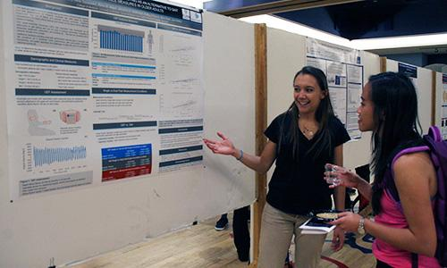Michelle Gary explains her research to a fellow student at BME Design Day on March 2