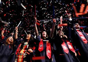 Graduates in caps and gowns throw confetti at UA Commencement