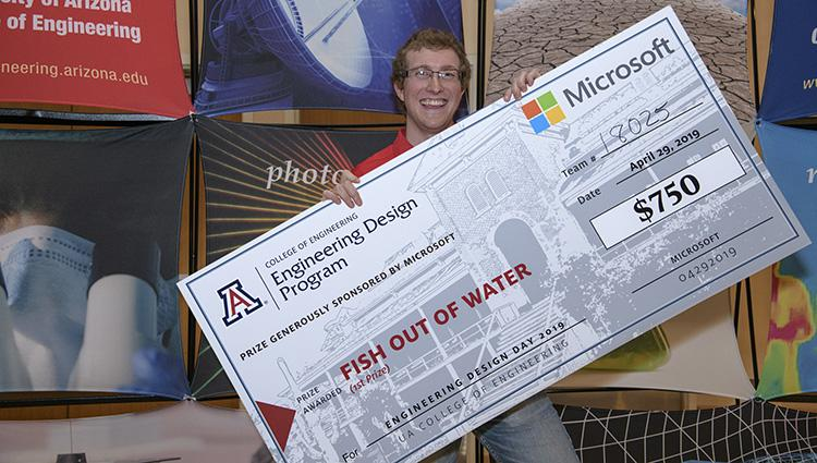 A smiling man holds a comically large check tilted across his chest
