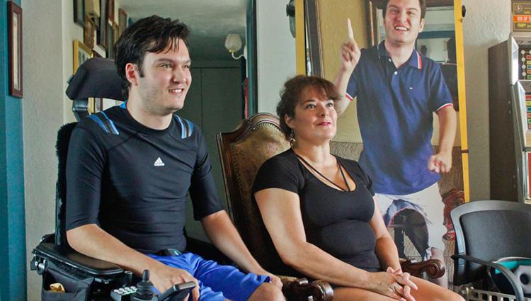 Jeffrey Bristol and his mother, Hermalinda, sit in their living room in Tucson. Jeffrey is wearing a dark blue athletic shirt and bright blue exercise shorts, sitting in a padded electric wheelchair.