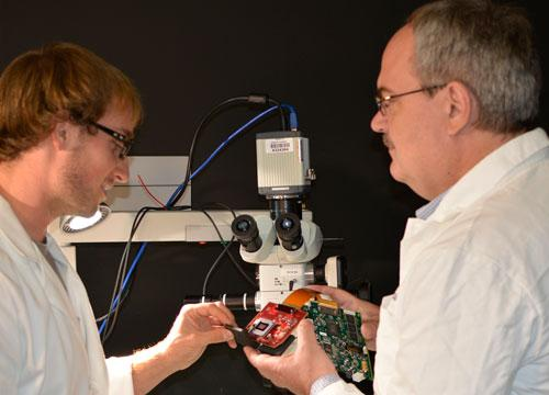Doctoral student Jeffrey Watson, left, and associate professor Marek Romanowski assemble parts for the prototype microscopy device.