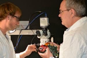Professor Marek Romanowski (right) assembles an augmented microscope with aid from doctoral student Jeffrey Watson. (2015)