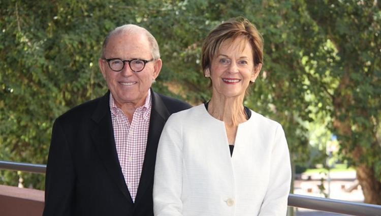 Peter and Nancy Salter stand together next to a railing in front of leafy green trees.