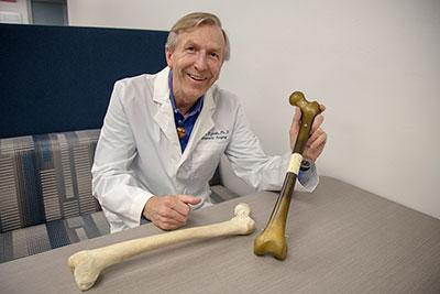 A man in a white lab coat posing with two large bones while sitting at a desk