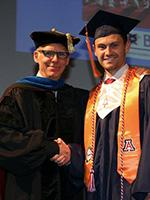 Department Head Art Gmitro shakes Tyler Toth's hand as he crosses the stage at BME's convocation ceremony